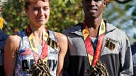 First-place female finisher Meghan Curran, left, from Moorestown, N.J., and first-place male finisher Samuel Kosgei, from Junction City, Kan., after the running of the 39th Marine Corps Marathon, in Arlington, Va., Oct. 26, 2014.