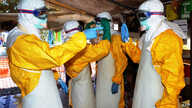 Guinea's health workers wearing protective suits join members of the Medecins sans frontieres Ebola treatement center near the main Donka hospital in Conakry on Sept. 25, 2014.
