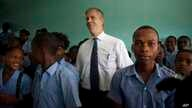 U.S. Secretary of Education Arne Duncan stands with students during his visit to Lycee de Petion-Ville high school in Petion-Ville, Haiti, Nov. 5, 2013.