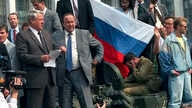 FILE -  In this Aug. 19, 1991, photo, Boris Yeltsin, foreground left, at the time president of the Russian constituent republic within the Soviet Union, addresses a crowd standing atop of a tank in front of the Russian Government Building, also known
