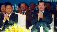Cambodian Prime Minister Hun Sen, front right, applauds together with the National Assembly President Heng Samrin, front left, during an event by the ruling Cambodian People's Party marking the 36th anniversary of the 1979 downfall of the Khmer Rouge