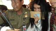 Kahiyang Ayu, daughter of Indonesian President Joko Widodo, is escorted by security as she arrives to take the civil service exam in the city of Solo, Central Java, Oct. 23, 2014. (Y. Satriawan / VOA)