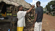 A community volunteer checks the temperature of a man before entering Jenewonde, in Liberia's Grand Cape Mount County, where local authorities say more than 20 people are suspected to have died of Ebola, Oct. 30, 2014.