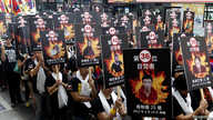 FILE - Activists displaying portraits of people who killed themselves in self-immolation take part in a rally to support Tibet in Taipei, March 10, 2013.