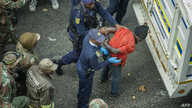 South African police officers, backed by soldiers, arrest illegal immigrants and foreign nationals during a raid in Johannesburg in the early morning hours of May 8, 2015.