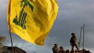 FILE - Israeli soldiers stand guard next to cameras at their new position in front of a Hezbollah flag, near the Lebanese southern border village of Mays al-Jabal, Lebanon, Dec. 13, 2018.