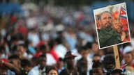 An image of Cuba's late President Fidel Castro is raised as people wait for the arrival of the caravan carrying Castro's ashes in Santiago de Cuba, Cuba, Dec. 3, 2016.