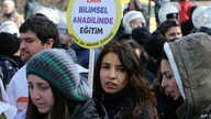 "FILE - A woman holds a placard demanding ""a secular and science-based education system"" as hundreds of students and teachers march at a rally in Ankara, Feb. 13, 2015."