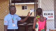FILE - An unidentified family member, right, of a 10-year-old boy that contracted Ebola, has her temperature  measured by a health worker before entering the Ebola clinic were the child is being treated on the outskirts of Monrovia, Liberia, Nov. 20,
