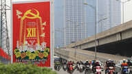 Vehicles drive past a sign marking the 12th Congress of the Communist Party of Vietnam in Hanoi, Vietnam, Jan. 19, 2016. This week, representatives of Vietnam's Communist party gather in the capital to pick the country's new leaders.
