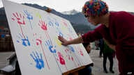 FILE - A Tibet supporter places his palm print on a banner during an event organized by Students for a Free Tibet to show solidarity with Tibetan political prisoners released in 2015 from Chinese jails in Dharmsala, India, Dec. 26, 2015.