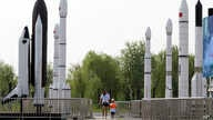 FILE - A woman walks with a child as they visit a park displaying replicas of foreign and domestic space vehicles in Beijing, China, June 26, 2016. China and the United States announced a new round of talks with China about civil space exploration.