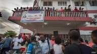 People mill around outside the APC headquarters in Sierra Leone. (O. Acland for VOA)