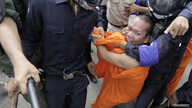 Cambodian police detain a Buddhist monk who was seeking the release of seven convicted land-rights activists in Phnom Penh, Nov. 11, 2014.