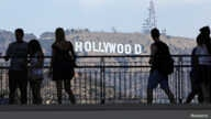 Tourists walk past the Hollywood sign as they visit a shopping complex along Hollywood