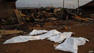 FILE - Dead bodies covered in plastic lie in front of a burnt out marketplace in Bor, South Sudan.