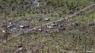 FILE - An aerial view of a coconut plantation and houses in a village destroyed by Typhoon Haiyan in Tolosa, Leyte in central Philippines, Nov. 19, 2013.
