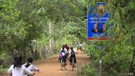 Children ride their bicycles past a sign bearing the Cambodian People's Party logo and the faces of Prime Minister Hun Sen and National Assembly President Heng Samrin in Banteay Meas village, Taches commune, Kampong Chhnang province, Nov. 8, 2017.