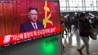 People walk past a television news broadcast at a railway station in Seoul on Jan. 1, 2017 showing North Korean leader Kim Jong-Un's New Year's speech.