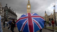A pedestrian shelters from the rain beneath a Union Jack-themed umbrella near the Big Ben clock face and the Elizabeth Tower at the Houses of Parliament in central London, following the pro-Brexit result of the UK's EU referendum vote, June 25, 2016....