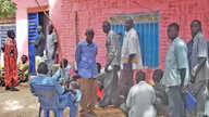 Dozens of South Sudanese returnees wait to pick up free national ID cards at Apada camp near Aweil in Northern Bahr el Ghazal on Tuesday, March 26, 2013. The cards, which usually cost US$11 are required when applying for a job or sitting exams in Sou