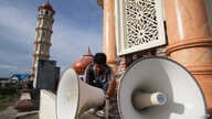 FILE – A worker inspects a loudspeaker at a mosque in Aceh