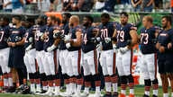 The Chicago Bears lock arms during the National Anthem in the first half of an NFL preseason football game against the Cincinnati Bengals, Aug. 9, 2018, in Cincinnati.