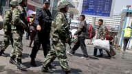FILE - Armed Chinese paramilitary policemen march past the site of an explosion outside the Urumqi South Railway Station in Urumqi in northwest China's Xinjiang Uygur Autonomous Region, May 1, 2014.