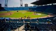 People work near a statue of Cuban baseball fan and entertainer Armando Luis Torres Torres at the Latinoamericano stadium, March 16, 2016. A friendly game will be played on March 22 between the Cuban national baseball team and the Tampa Bay Rays, in