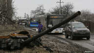 Empty buses wait along a road beside a burnt-out tank turret while travelling in the direction of Debaltseve to evacuate the residents, in Vuhlehirsk, Donetsk region,  Feb. 6, 2015.