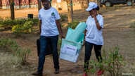 Polling staff carry a ballot box before counting at a polling center in Kigali, Rwanda, Aug. 4, 2017.