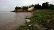 FILE - A Cambodian fisherman takes off his fishing net at Mekong river bank of Koh Norea village in Phnom Penh.