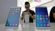 FILE - A journalist takes a picture of China's mobile company Xiaomi's new model Mi Max at its launching ceremony in Beijing, May 10, 2016.