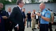In this photograph made available by the Serbian Presidency, a Kosovo police officer speaks to Serbia's president Aleksandar Vucic, left, to say he cannot continue his trip to the village of Banje due to roadblocks, in Zubin Potok, Kosovo, Sept. 9, 2...