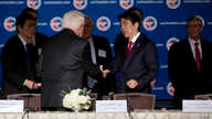 Japanese Prime Minister Shinzo Abe is greeted by U.S. Chamber of Commerce President and CEO Tom Donohue, left, as he arrives at a meeting at the U.S. Chamber of Commerce in Washington, April 29, 2015.