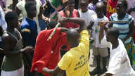 A youth is beaten with sticks after being accused of attempted theft in Monrovia, February 2007.