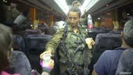 An Israeli solider hands out water on a bus, during the Syria Civil Defense, also known as the White Helmets, evacuation from the Golan Heights, Israel, in this still image taken from video, provided by the Israeli Army, July 22, 2018.