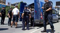 FILE - Kosovo police officers escort a Kosovo Albanian man suspected of fighting alongside Islamic radicals in Iraq and Syria to a local court in Pristina, Tuesday, Aug. 12, 2014. Kosovo police on Monday arrested at least 40 people in a major operati