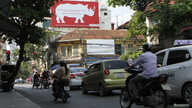 A giant poster, encouraging passers-by to stop using rhino horn, is seen on a street in Hanoi, Sept. 22, 2014.