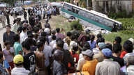 Crowds of people watch a bus collided with a motorcycle on the outskirts of Phnom Penh, Cambodia, Sept. 24, 2009.