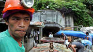 FILE - A mine worker watches the ongoing recovery operation after an explosion inside the tunnel in a collapsed gold mine in Mt. Diwata in Compostela Valley province, Philippines.