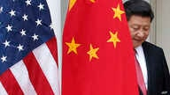 Chinese President Xi Jinping steps out from behind China's flag as he takes his position for his joint news conference with President Barack Obama in the Rose Garden of the White House in Washington, Sept. 25, 2015.