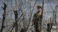FILE - A North Korean prison policewoman stands guard behind fences at a jail on the banks of Yalu River near the Chongsong county of North Korea, opposite the Chinese border city of Dandong.