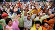 Cambodians raise their arms as they gather during a protest at Freedom Park in central Phnom Penh, Dec. 17, 2013.