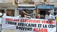 "Protesters gather outside the Gambian Embassy in Senegal on August 30, 2012. The banner reads : "" Stop summary executions. The African Union and ECOWAS must react."""