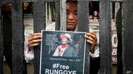 FILE - An exile Tibetan poses as Runggye Adak as he stands behind bars depicting jail during a street performance by Tibetan activists in Dharmsala, India, Aug.1, 2014.