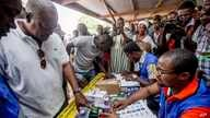 Ghana Incumbent President, John Dramani Mahama candidate of the National Democratic Congress, second left, validates his name before casting his vote during the Presidential and parliamentary election, in Bole Ghana, Wednesday, Dec. 7, 2016.