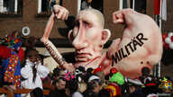 "A carnival float with a paper-mache caricature of Russian President Vladimir Putin moves past revellers during a carnival parade in Duesseldorf, Germany, Feb.16, 2015. The text on the caricature's right arm reads ""military;"" the text on its left arm"