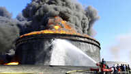 Firefighters train hoses on a flaming oil storage tank in Es Sider a month ago. The fire began when militias in attack vessels fired missiles at the storage facility.