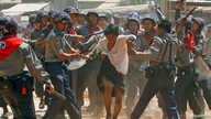 Police hit a student protester during violence in Letpadan March 10, 2015. Myanmar police beat students with batons and detained some of them as they broke up a group of about 200 protesters who had been locked in a standoff with security forces for